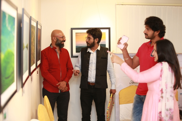 visitors having a look at the pictures at the exhibition_ Shiv Gandhi seen in red shirt